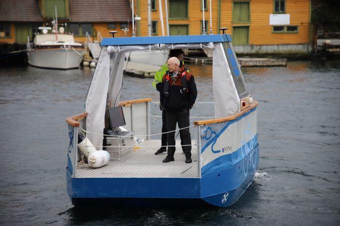 Førsteamanuensis Egil Eide og student Tobias Torben (gul jakke) tar en piruett med Milliampere i Smedasundet i Haugesund etter demonstrasjonen av autonomi-fergen for Sjøfartsdirektoratet.