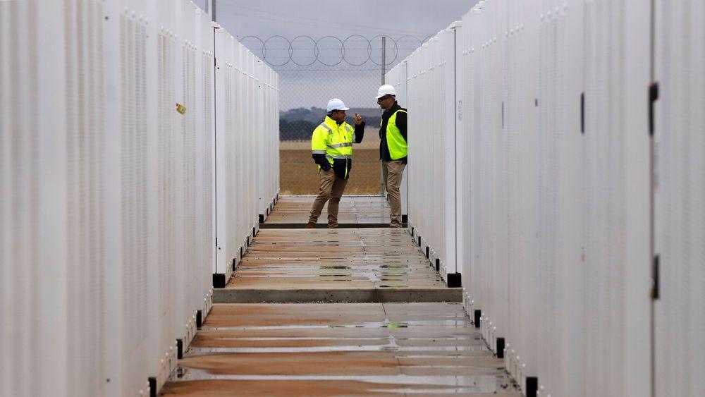 Teslas kjempebatteri i Australia har vist seg å være god butikk for franske Neoen. Her står noen arbeidere bak gjerdet til Hornsdale Power Reserve, som huser verdens største litiumionebatteri. Bildet er fra januar 2017.