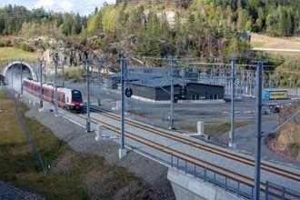 Tog som kommer ut av Nøklegårdtunnelen og passerer Solum omformerstasjon