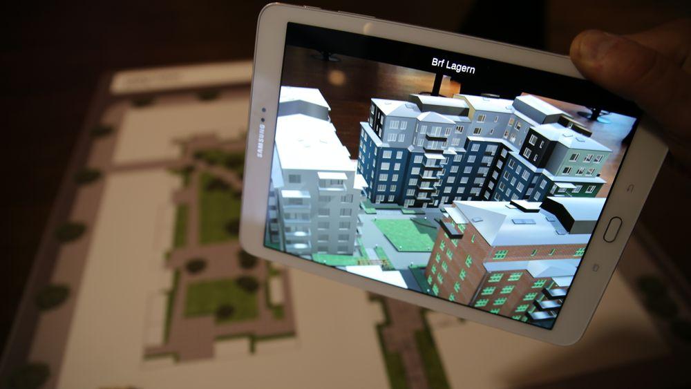 En AR-app får 3D-modellene til å vise seg på skjermen når du retter den mot plantegningen. Modellen til venstre er hvit i dette tilfellet fordi den tilhører et påfølgende byggetrinn.