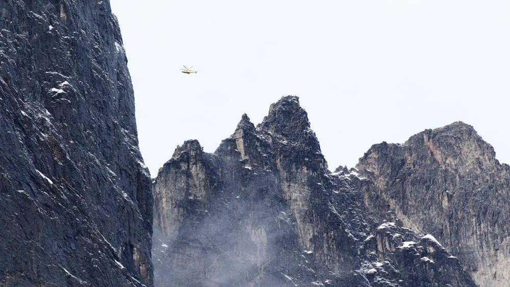 Et helikopter flyr over fjellene rundt Veslemannen i fjellpartiet Mannen i Rauma kommune i Møre og Romsdal.