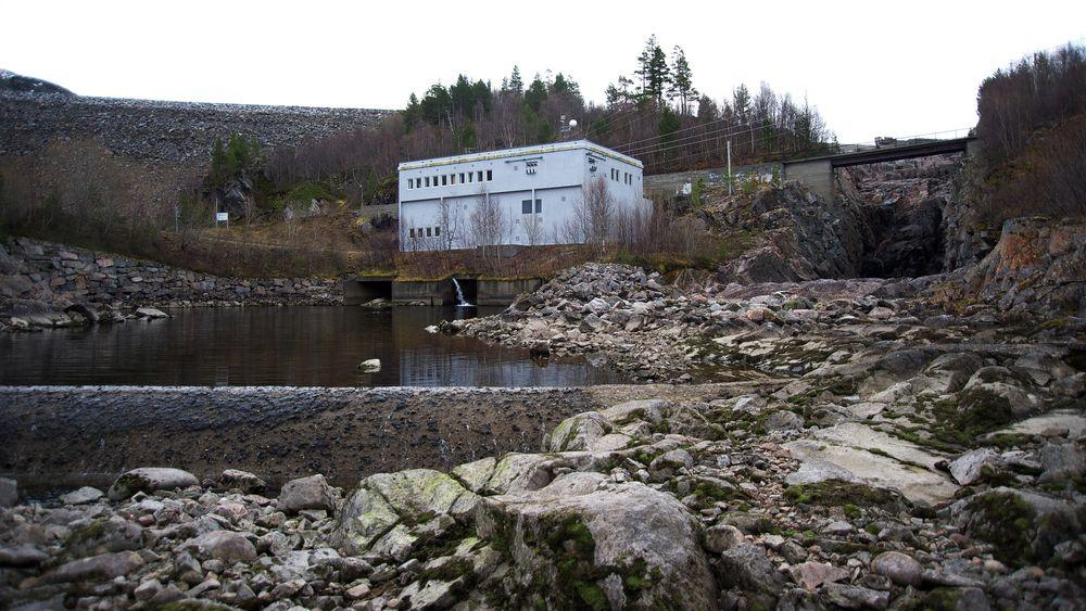Elva Surna i Surnadal på Nordmøre er nasjonal lakseelv, men også regulert for kraftproduksjon. Det har vært flere konflikter mellom elveeiere, laksefiskere og kraftverkseier Statkraft. Bildet viser Gråsjø kraftverk, som utnytter fallet fra Gråsjøen til Follsjø. Gråsjødammen som vises bak kraftverket.