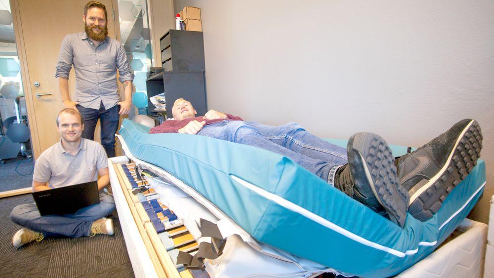 Andreas Smith (sittende) demonstrerer hvordan pasienten vil ligge på forsøkskanin Bjørn Lorentzen. Arvid Bjerre følger med at alt virker som det skal.