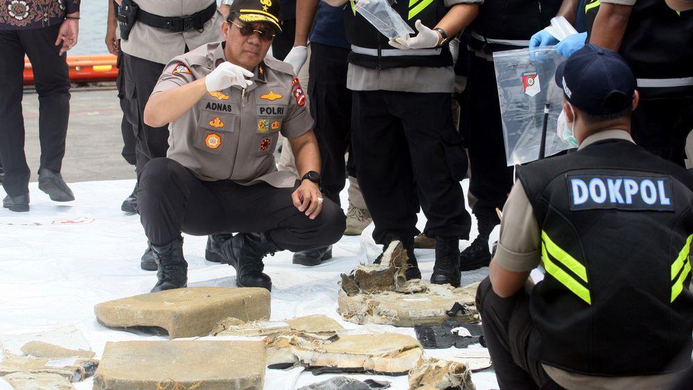 Vrakrester etter gårsdagens flystyrt undersøkes av indonesisk personell.