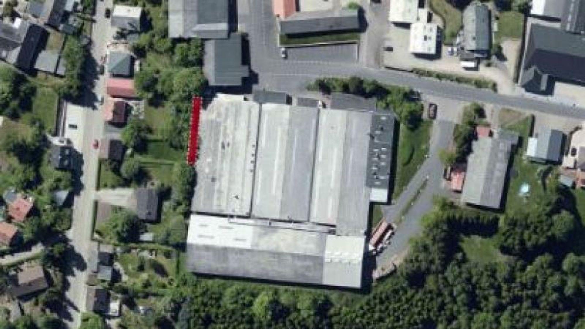 Den røde markeringen viser hvor entreprenørmaskiner borer opp 200 tonn forurenset jord i den danske småbyen Them. De fire store produksjonsbygningene er sykkelprodusenten Winther.