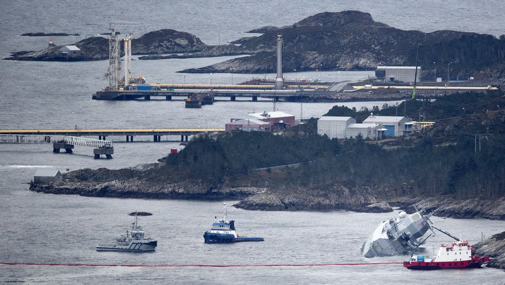 """Den norske fregatten """"KNM Helge Ingstad"""" ligger med slagside nær land etter at den kolliderte med tankskipet """"Sola"""" natt til torsdag. Deler av Stureterminalen i bakgrunnen."""