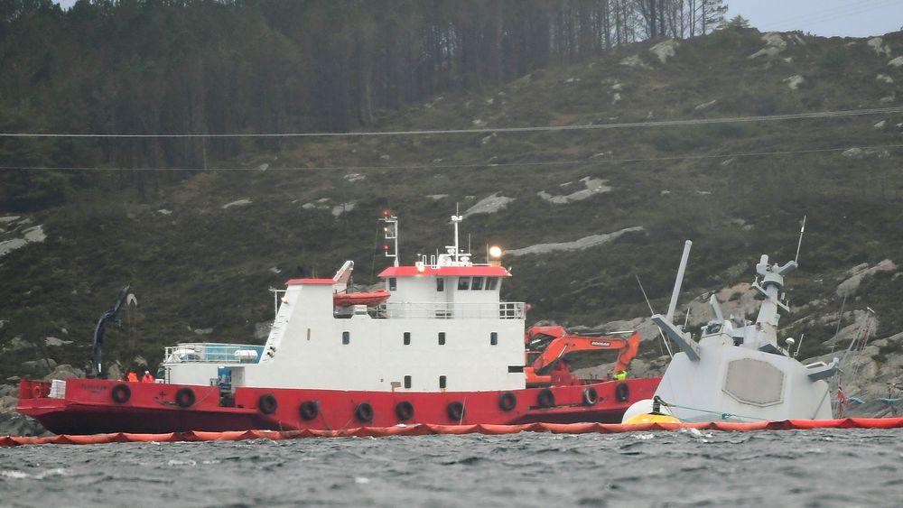 En båt med bergingsmannskaper ved den havarerte fregatten. Helge Ingstad ligger nå nesten helt under vann, etter at flere vaiere som har holdt skipet fast, har løsnet.