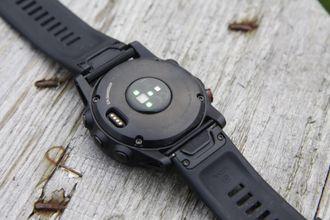 Fenix 5X Plus har en optisk pulsmåler på undersiden. Til venstre ser du ladekontakten.