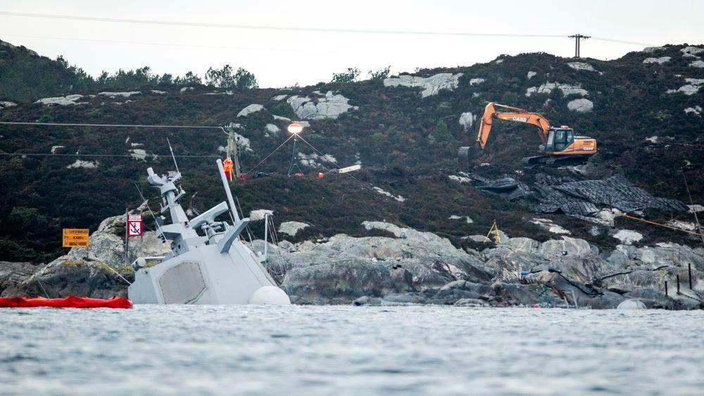 Det pågår arbeider i land rett ved der fregatten KNM Helge Ingstad ligger. En gravemaskin legger på plass sprengmatter oppå fjellet og det er trukket gule tau ut til akterenden av havaristen som så vidt stikker opp av vannet. Foto: Tore Meek / NTB scanpix