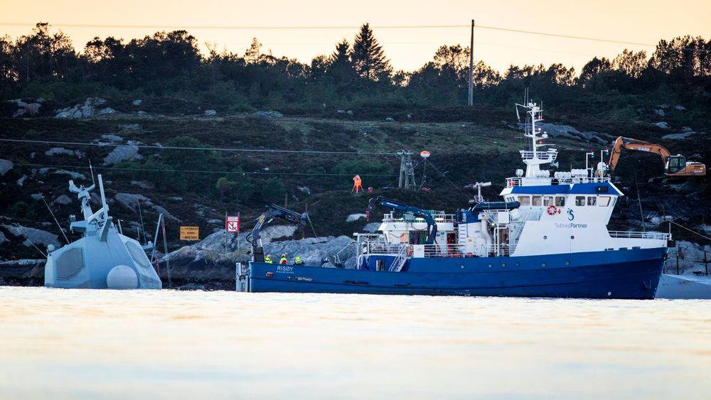 Dykkerbåten Risøy fra Subsea Partner ved vraket av KNM Helge Ingstad. Arbeidet med å tmme fregatten for drivstoff er nå i gang.