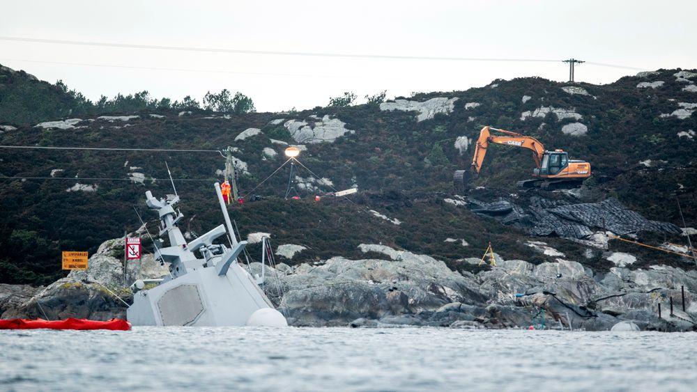 Det pågår arbeider i land rett ved der fregatten KNM Helge Ingstad ligger. En gravemaskin legger på plass sprengmatter oppå fjellet og det er trukket gule tau ut til akterenden av havaristen som så vidt stikker opp av vannet.Foto: Tore Meek / NTB scanpix