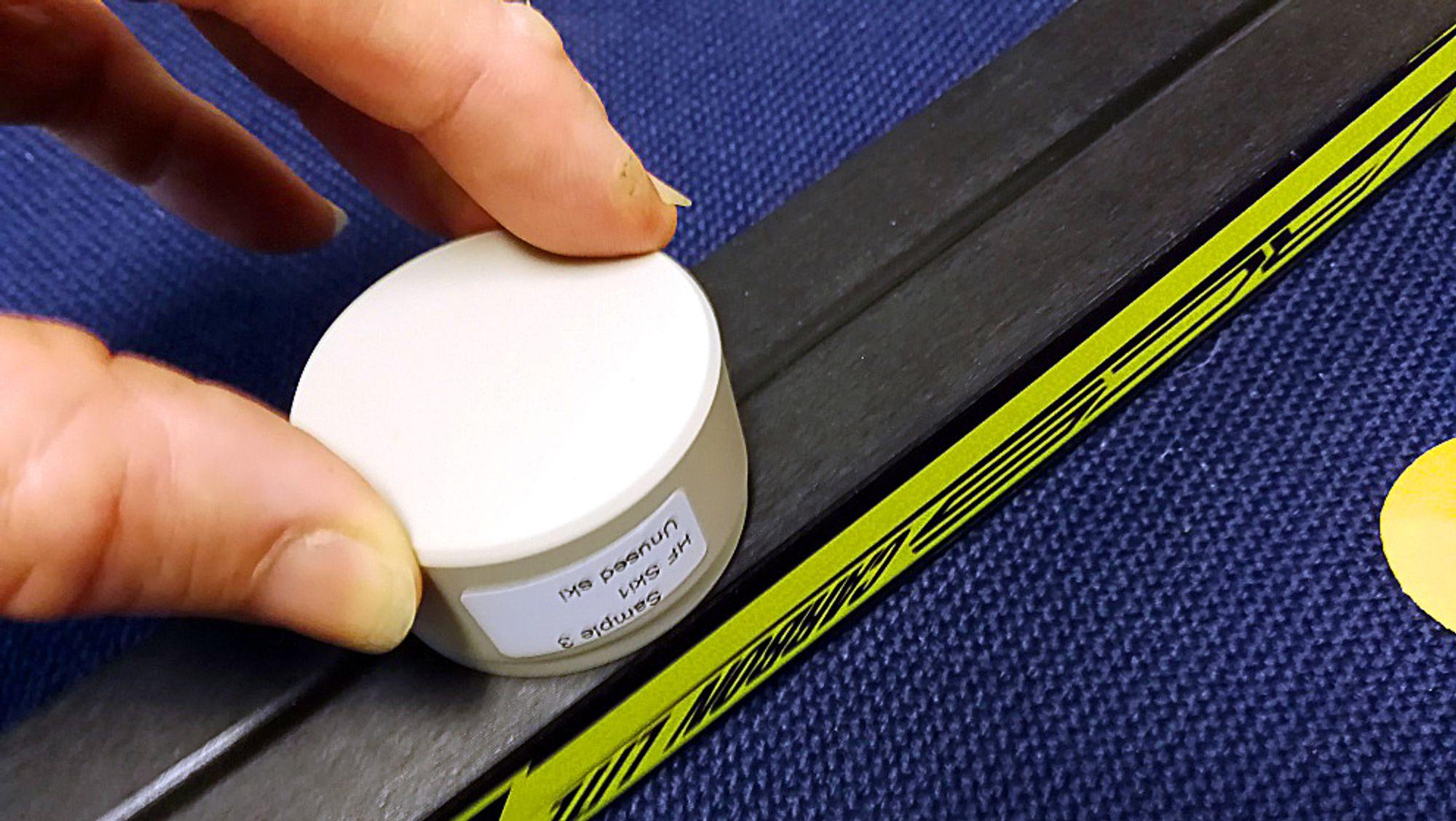 Testing: Ved å dytte en teipbit festet til en prøveholder mot skisålen, kan man etter noen sekunder i et spektroskop se om skien er glidet med fluor. Foto: NILU