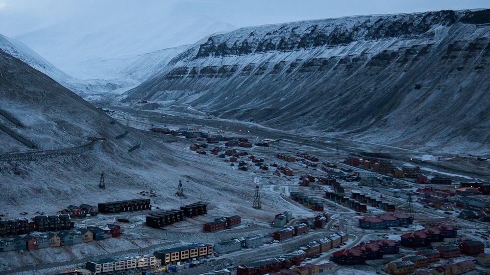 Longyearbyen med Sukkertoppen til venstre. Store snømengder raste ned fra fjellet i desember 2015, og knuste ti hus i området midt på bildet. Nede til venstre bygges nye, skredsikre boliger.