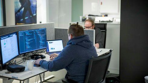 To utviklere sitter foran skjermer og programmerer.