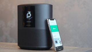 Bose Home Speaker 500-høyttaleren ved siden av en iPhone XS-mobiltelefon med Spotify på skjermen.