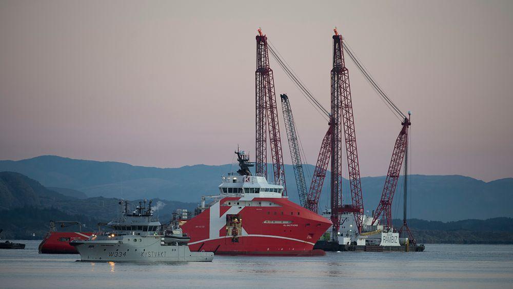 Kranbåten Rambiz ligger ved den havarerte KNM Helge Ingstad for å forberede bergingen. Nå har en av vaierne som holder skipet, røket.