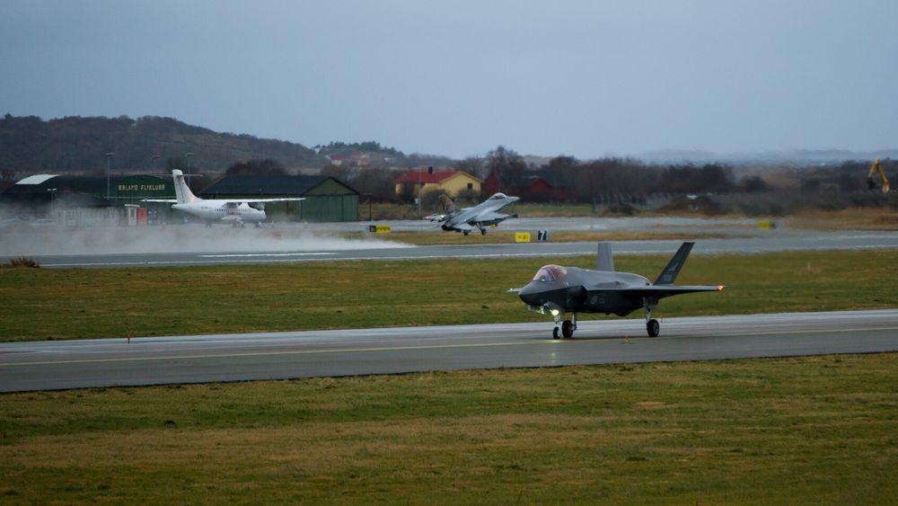 En F-35A takser på Ørland flystasjon samtidig som et F-16 tar av. På den sivile sida står et ATR-42 parkert.