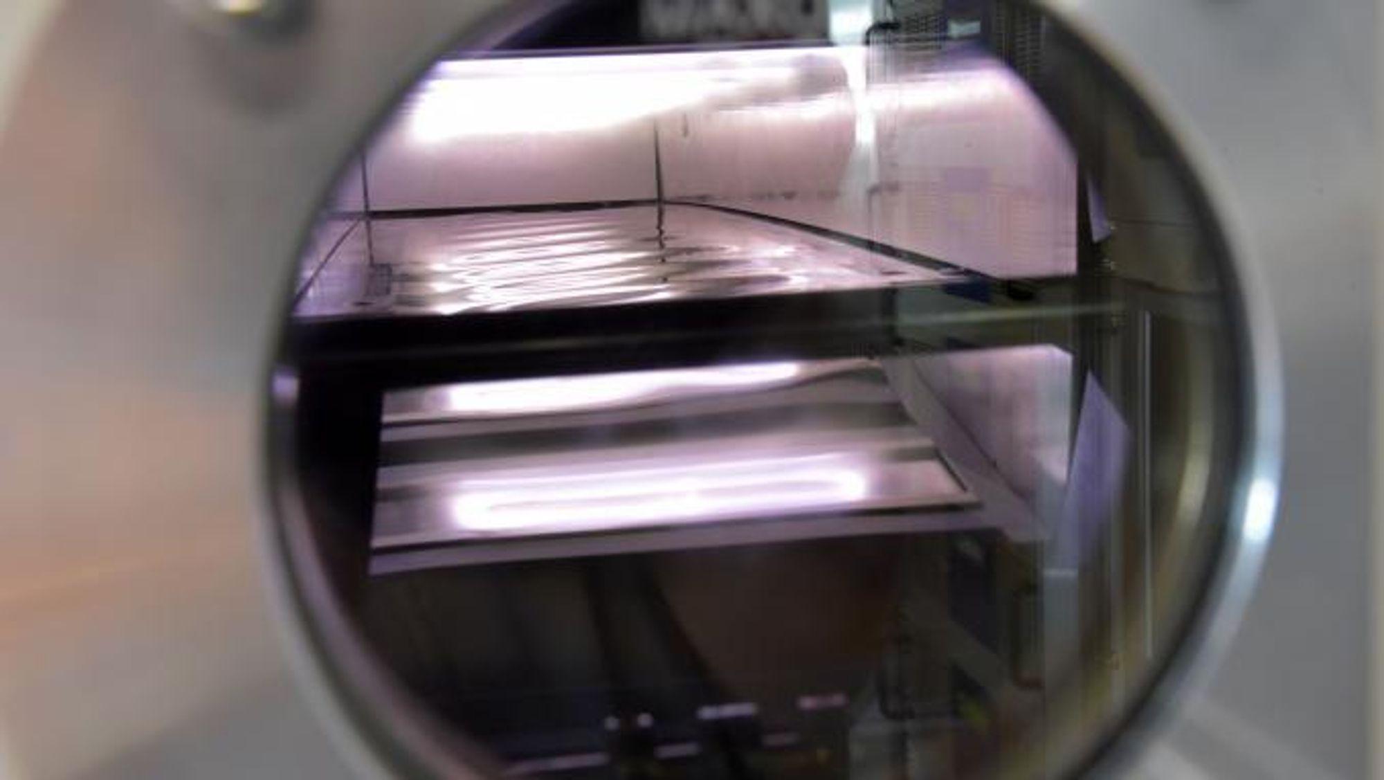 En solcelle utsettes for såkalt reactive sputtering (reaktiv katodeforstøvning). Prosjektet er bl.a. støttet av Danmarks Frie Forskningsfond og Villum Fonden.