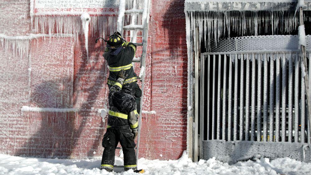En brannmann støttes opp av en kollega mens kan kapper is av en stige etter å ha bidratt til å slukke en boligbrann i Newark, USA.