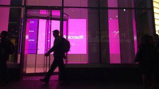 Silhuett av mennesker som går foran opplyste vinduer med stor Microsoft-logo, ved Microsofts kontor i New York.