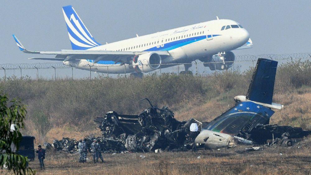 Det utbrente Q400-vraket ligger utenfor rullebanen i Katmandu med et A320 fra Himalaya airlines i bakgrunnen.