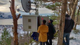 Tre personer i ved parabolantenne og stor boks som inneholder utstyr for videreformidling av signaler via 4G eller 5G.