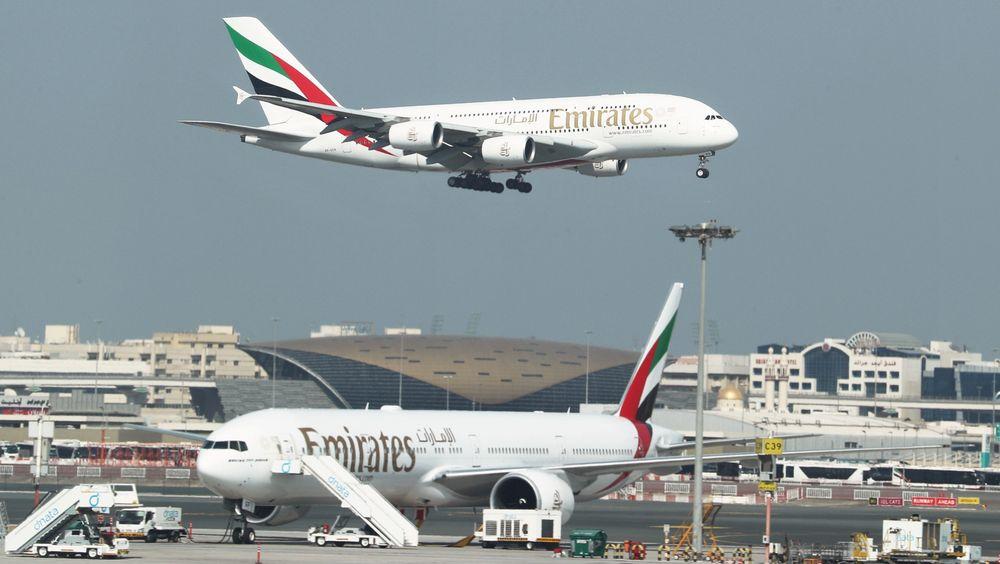 Et A380-800 går inn for landing i Dubai, der det står et B777-300ER parkert.