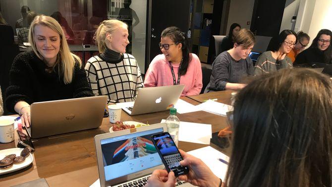 Studenter løser oppgaver sammen rundt et bord.