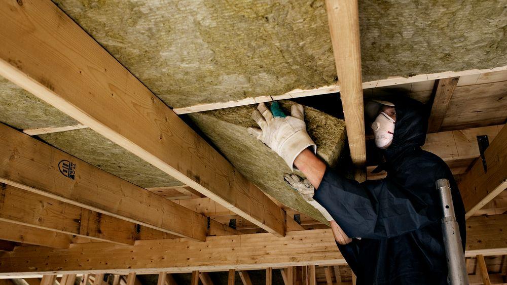 Håndverkere er igang med å legge isolering i et hus i København.