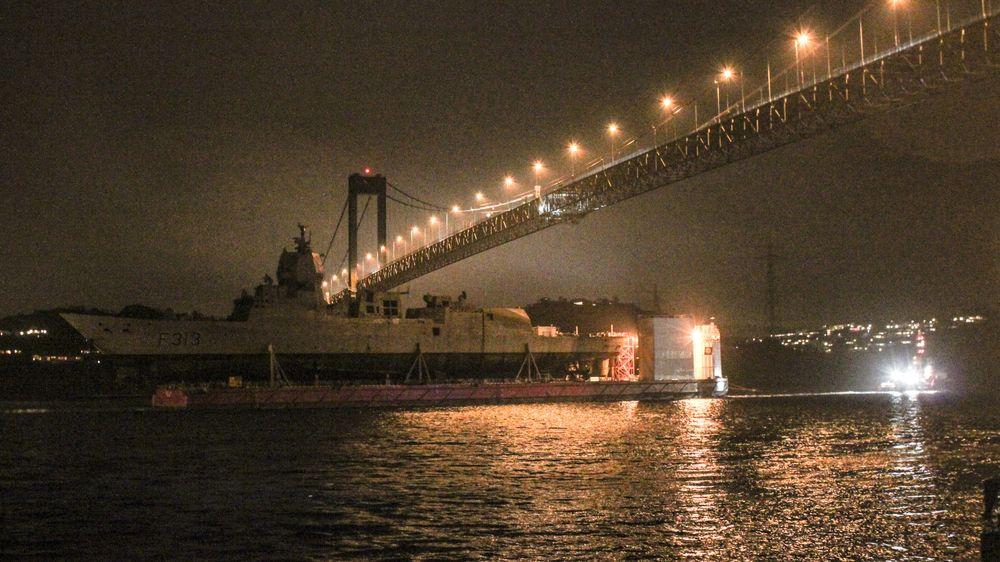 Lekteren Boabarge 33 med den forliste fregatten KNM Helge Ingstad passerer under Sotrabrua på sin vei mot Haakonsvern søndag kveld.