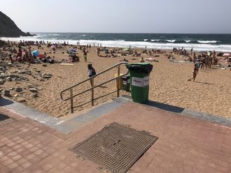 Fiberkabelen kommer i land på denne stranden i Baskerland. Det står «fiberoptisk kabel» på lokket i forkant av bildet.