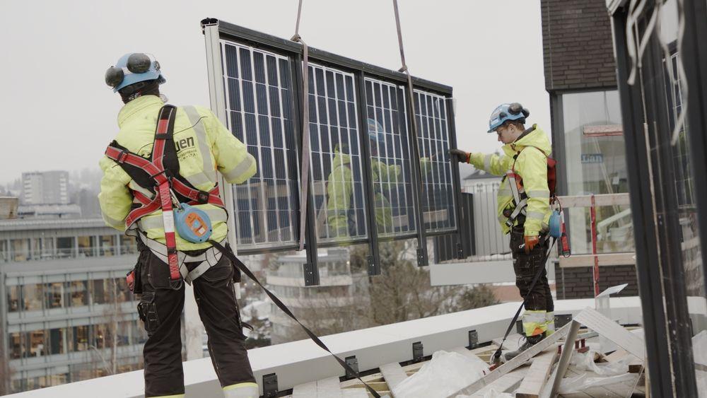 Montørene Per Lyngklip (til venstre) og Nerijus Unikauskas fra Sagstuen monterer det første serieproduserte solcellerekkverket på Orklas nye hovedkvarter i Oslo.
