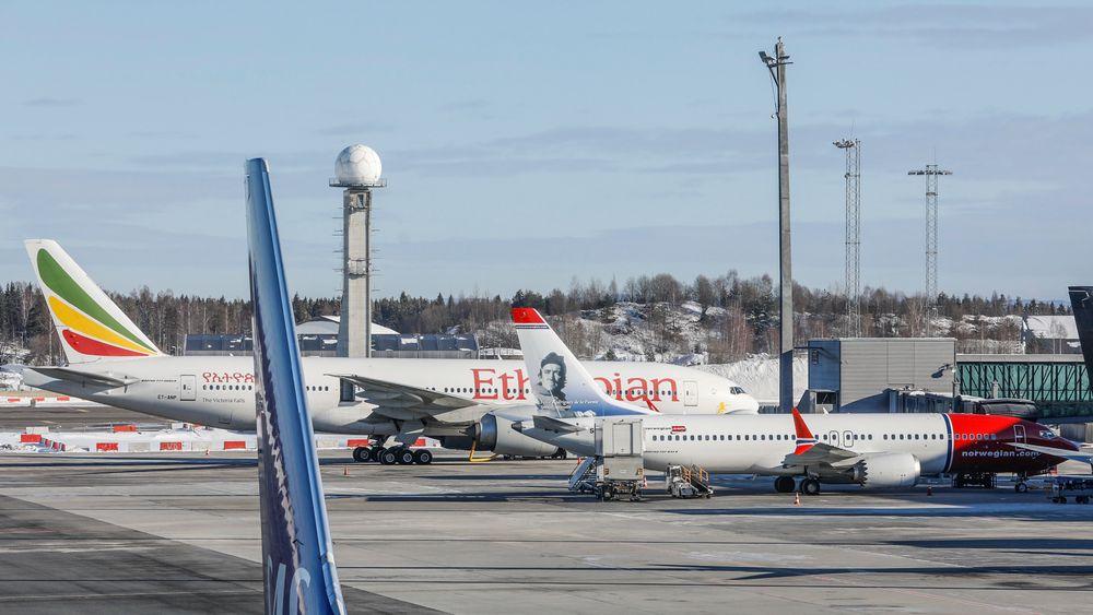 Et Boeing 737 Max-8-fly fra Norwegian (SE-RTC) står ved gaten på Oslo lufthavn. Bak står et Boeing 777-260 LR (ET-ANP) fra Ethiopian Airlines.