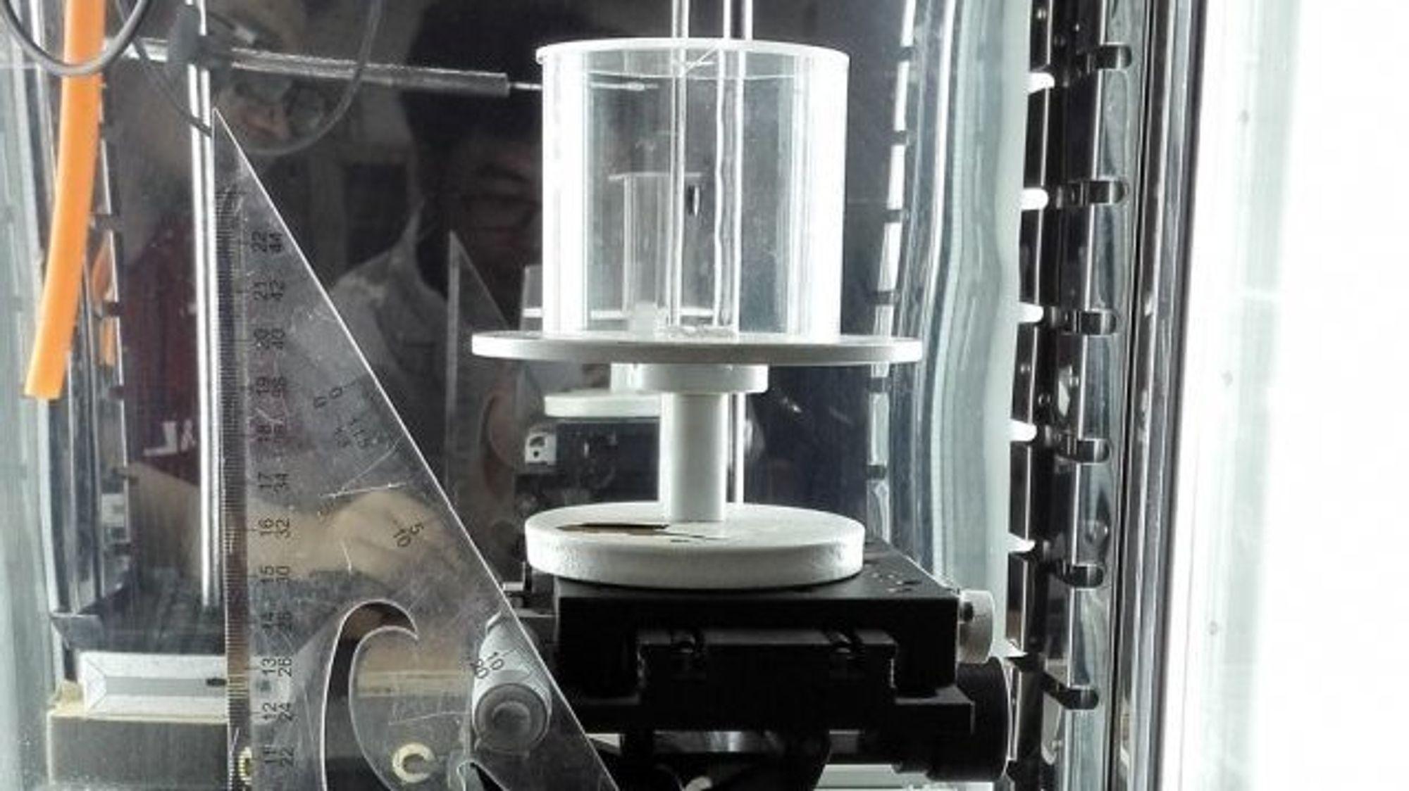 Laboppsettet som er brukt til å teste hvordan edderkoppspinnet oppfører seg under forskjellige forhold. Den lukkede glassylinderen gjør det mulig å kontrollere fuktigheten nøyaktig mens man tester sammentrekning og vridning på tråden.Credit: Photo courtesy of the researchers