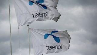 Telenor-flagg mot mørk himmel, mørke skyer.