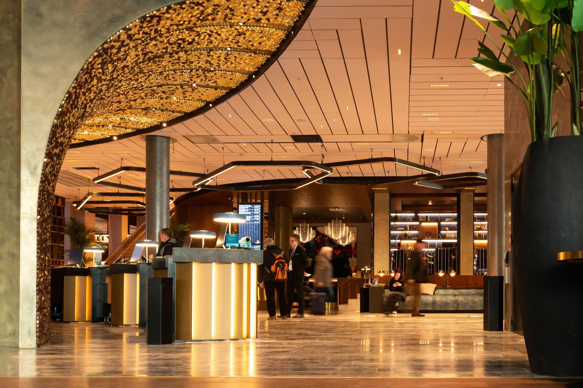 Resepsjonsområdet til et hotell kan være preget av mye støy. Elegante himlingsløsninger sørger for både god akustikk og estetikk.