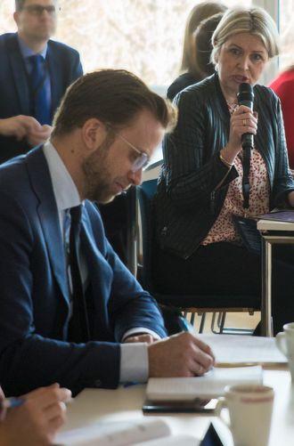 Nikolai Astrup noterer mens Kristin Vinje snakker til ham i bakgrunnen.
