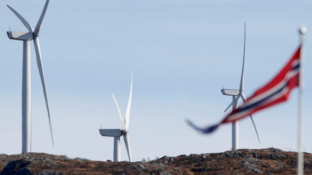 Vimpel i Fitjar sentrum med tre av vindturbinene i Midtfjellet vindpark i Fitjar kommune i bakgrunnen.
