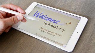 Hånd som skriver på en iPad mini med Apples penn.