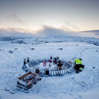 En elektriker arbeider med fundamentet til en vindturbin i Roan vindpark i desember. Fjelltoppen er dekket av snø.