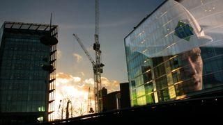 vilde av glassbygg med refleksjon av mann med byggehjelm