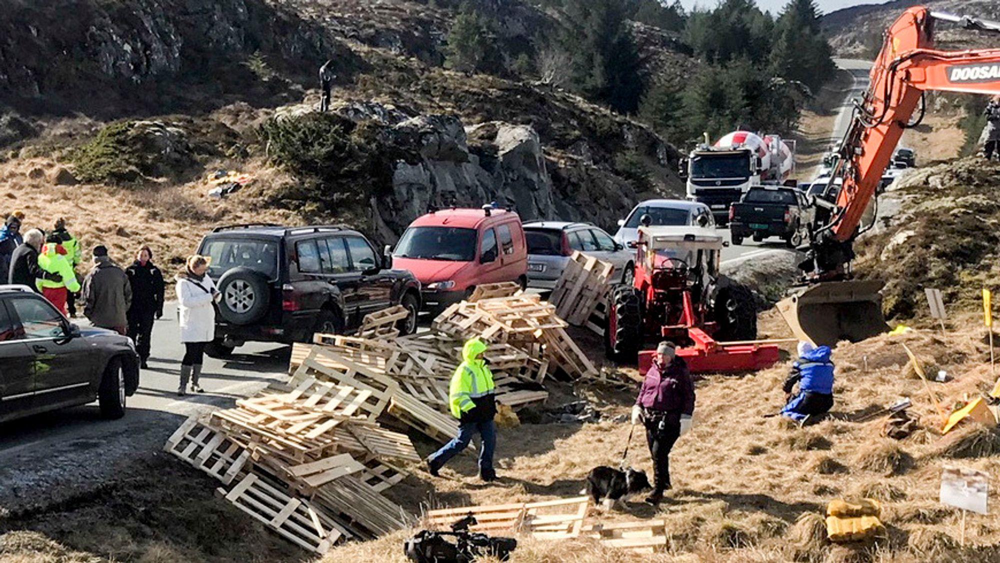 Politiet har bøtelagt demonstrantenes biler som står langs veien på Frøya. Pallene som ble levert av Salmar-eier Gustav Witzøe ble brukt til å hindre anleggstrafikk til å kjøre forbi.