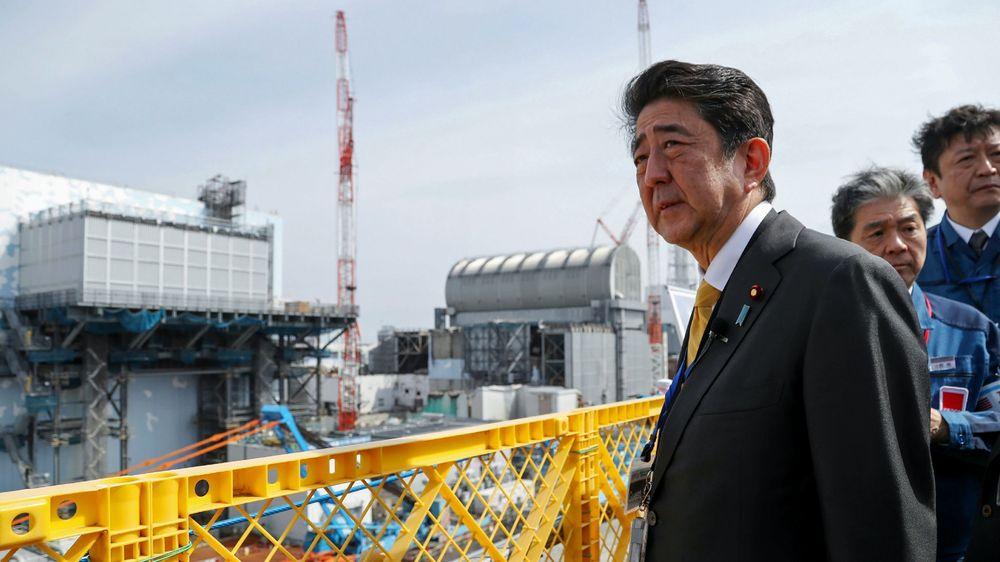 Japans statsminister Shinzo Abe besøkte atomkraftverket i Okuma søndag. Her står Abe utenfor reaktor nummer 2 (til venstre) og nummer 3 (til høyre).
