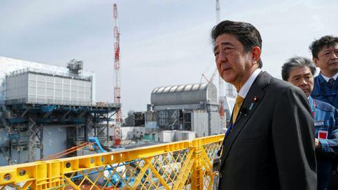 Foto av mann foran atomkraftverk. Japans statsminister.