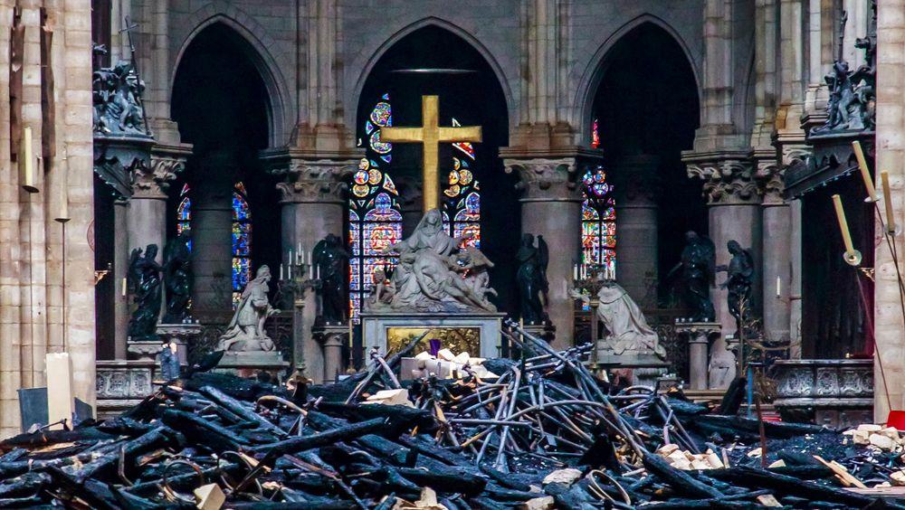Utbrente rester av taket ligger inne i Notre-Dame dagen etter brannen mandag. Det som ser ut som intakte vokslys, står på staker i kantene av bildet.