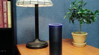 Illustrasjonsfoto av Amazons Echo på et bord med plante og lampe i bakgrunnen.