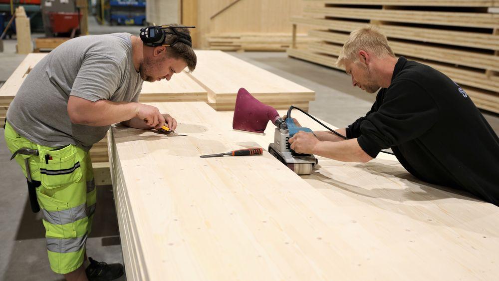Jørgen Evenstuen og Morten Th. Strandved fjerner limrester og gir massivtrplatene en siste finpuss. Det er den eneste menneskekontakten platene får i den automatiserte prosessen.