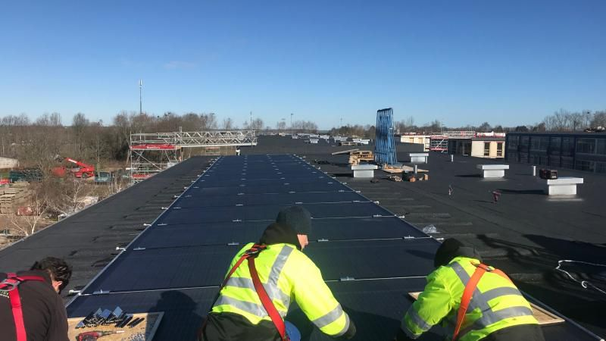 På taket av en boligblokk i Aarhus settes det opp solcellepaneler som er både solfangere og varmevekslere til varmepumpene i bygningen.