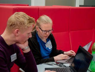 To deltakere sitter og ser sammen på to dataskjermer. Foto.