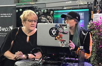 Trine Skei Grande og en kvinnelig TG-deltaker ser på en laptop-skjerm.